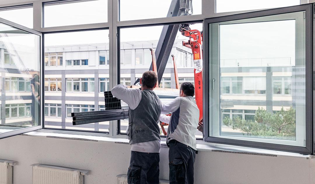 Kran lädt Baustoffe durch ein Fenster