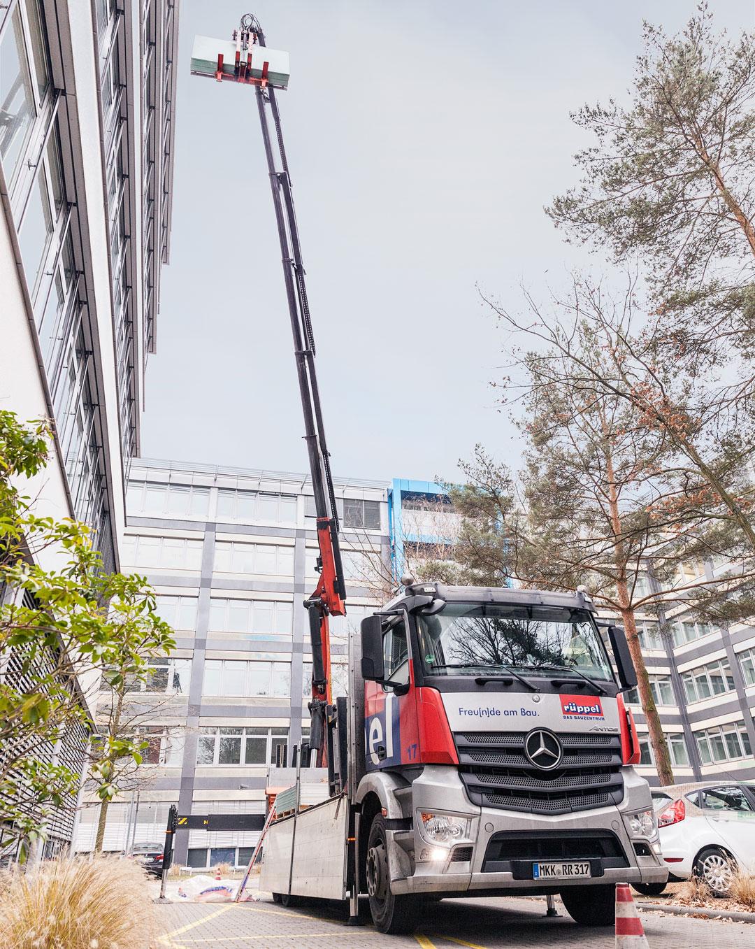 LKW mit Kran beliefert ein Gebäude